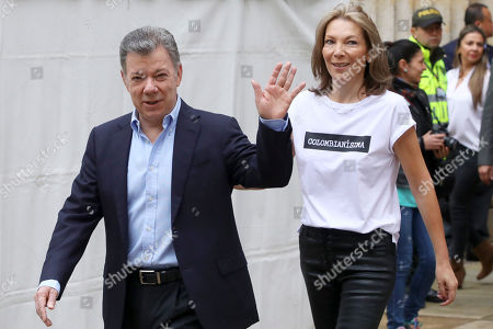 Colombia's President Juan Manuel Santos waves as he arrives with his wife, Maria Clemencia Rodriguez, to vote in a presidential runoff election in Bogota, Colombia, . Voters will choose between Ivan Duque, a young conservative lawmaker, and Gustavo Petro, a leftist former guerrilla and ex-Bogota mayor
