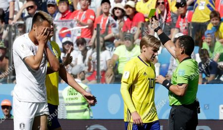 Kim Shin-Wook, Joel Aguilar. Referee Joel Aguilar, right, shows a yellow card to Kim Shin-Wook, left, during the group F match between Sweden and South Korea at the 2018 soccer World Cup in the Nizhny Novgorod stadium in Nizhny Novgorod, Russia