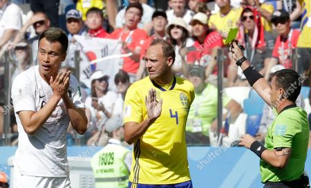 Kim Shin-Wook, Joel Aguilar. South Korea's Kim Shin-wook, left, reacts as Referee Joel Aguilar, right, shows a yellow card during the group F match between Sweden and South Korea at the 2018 soccer World Cup in the Nizhny Novgorod stadium in Nizhny Novgorod, Russia