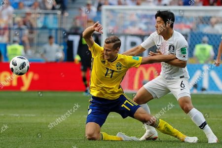 Sweden's Viktor Claesson, left, is challenged by South Korea's Park Joo-ho during the group F match between Sweden and South Korea at the 2018 soccer World Cup in the Nizhny Novgorod stadium in Nizhny Novgorod, Russia