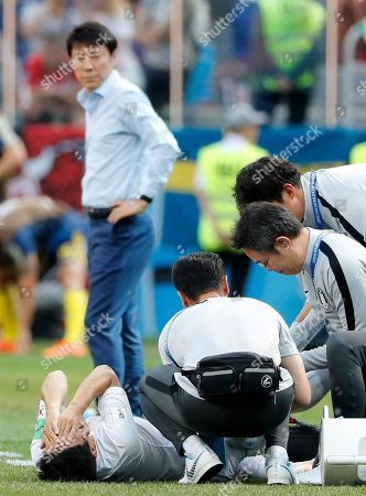 South Korea's head coach Shin Tae-yong looks at South Korea's Park Joo-ho who reacts after getting injured during the group F match between Sweden and South Korea at the 2018 soccer World Cup in the Nizhny Novgorod stadium in Nizhny Novgorod, Russia