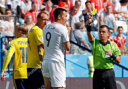 Referee Joel Aguilar from El Salvador gives a yellow card to South Korea's Kim Shin-wook during the group F match between Sweden and South Korea at the 2018 soccer World Cup in the Nizhny Novgorod stadium in Nizhny Novgorod, Russia