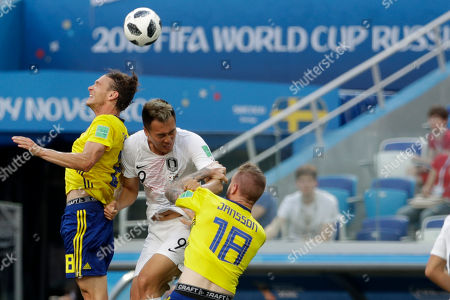 South Korea's Kim Shin-wook, jumps for the ball against Sweden's Albin Ekdal, left, and Sweden's Pontus Jansson during the group F match between Sweden and South Korea at the 2018 soccer World Cup in the Nizhny Novgorod stadium in Nizhny Novgorod, Russia