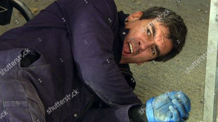 Stock Photo of Ep 8190 Friday 29th June 2018 Cain Dingle, as played by Jeff Hordley, is busy working on a car when out of the blue is hit to the floor. We then see a bloodied and bruised Simon, as played by Liam Ainsworth, menacing as he raises a spanner to hit Cain once again.