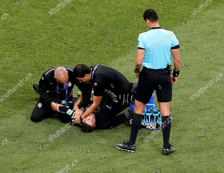 Goalkeeper Mouez Hassen of Tunisia (2-L) receives medical assistance during the FIFA World Cup 2018 group G preliminary round soccer match between Tunisia and England in Volgograd, Russia, 18 June 2018. (RESTRICTIONS APPLY: Editorial Use Only, not used in association with any commercial entity - Images must not be used in any form of alert service or push service of any kind including via mobile alert services, downloads to mobile devices or MMS messaging - Images must appear as still images and must not emulate match action video footage - No alteration is made to, and no text or image is superimposed over, any published image which: (a) intentionally obscures or removes a sponsor identification image; or (b) adds or overlays the commercial identification of any third party which is not officially associated with the FIFA World Cup)