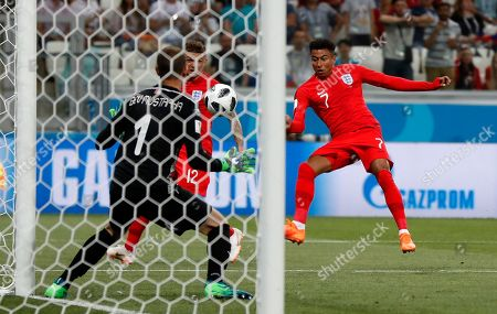 England's Jesse Lingard kicks the ball to Tunisia goalkeeper Mouez Hassen during the group G match between Tunisia and England at the 2018 soccer World Cup in the Volgograd Arena in Volgograd, Russia