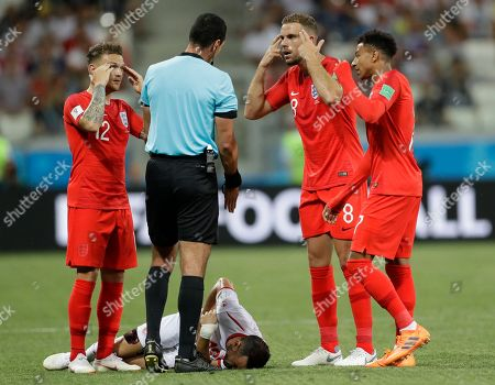 England's Kieran Trippier, left, Jordan Henderson and Jesse Lingard, right, gesture while speaking to a referee as Tunisia's Ali Maaloul lies on the field during the group G match between Tunisia and England at the 2018 soccer World Cup in the Volgograd Arena in Volgograd, Russia