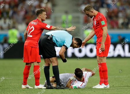 England's Kieran Trippier, left, and England's Jordan Henderson, right, gesture as a referee speaks to Tunisia's Ali Maaloul lies on the field during the group G match between Tunisia and England at the 2018 soccer World Cup in the Volgograd Arena in Volgograd, Russia