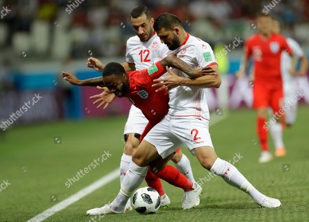 England's Raheem Sterling, left in red, fights for the ball with Tunisia's Ali Maaloul, center, and Tunisia's Syam Ben Youssef, right, during the group G match between Tunisia and England at the 2018 soccer World Cup in the Volgograd Arena in Volgograd, Russia