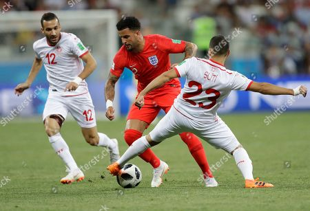 England's Kyle Walker, center, vies for the ball with Tunisia's Ali Maaloul, left, and Tunisia's Naim Sliti during the group G match between Tunisia and England at the 2018 soccer World Cup in the Volgograd Arena in Volgograd, Russia
