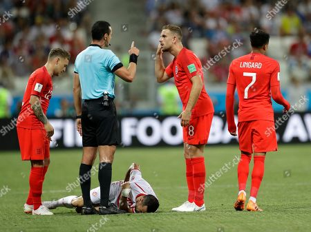 A referee points while speaking to England's Jordan Henderson as Tunisia's Ali Maaloul lies on the field during the group G match between Tunisia and England at the 2018 soccer World Cup in the Volgograd Arena in Volgograd, Russia