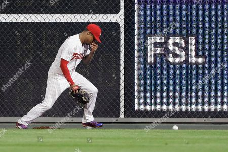Philadelphia Phillies right fielder Nick Williams reacts after being hit by the ball on a double by St. Louis Cardinals' Matt Carpenter during the eighth inning of a baseball game, in Philadelphia. Philadelphia won 6-5 in 10 innings
