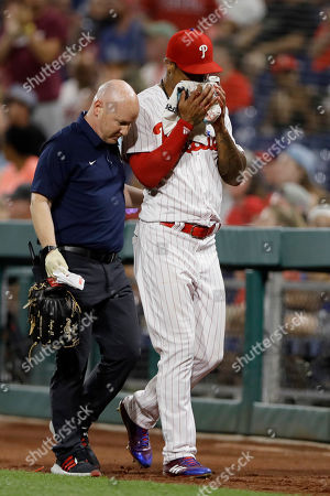 Philadelphia Phillies right fielder Nick Williams, right, is helped off the field after being injured on a double by St. Louis Cardinals' Matt Carpenter during the eighth inning of a baseball game, in Philadelphia. Philadelphia won 6-5 in 10 innings