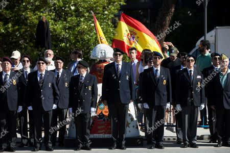 Veteran soldiers stand to attention next to a figure of one of the 'Meninas' (Ladies in waiting), based on the 1656 painting by Diego Velazquez during the flag-raising ceremony celebrating the 4th anniversary of the proclamation of Spain's King Felipe VI, at the Colon Plaza in Madrid, Spain