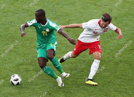 Grzegorz Krychowiak of Poland and Moussa Konate of Senegal
