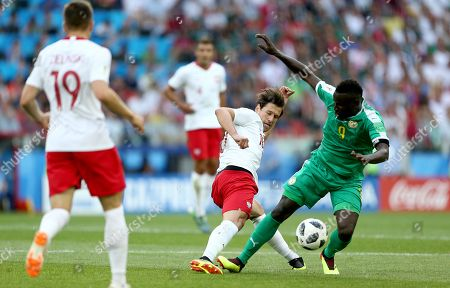 Grzegorz Krychowiak of Poland is booked for this tackle on Mame Biram Diouf of Senegal