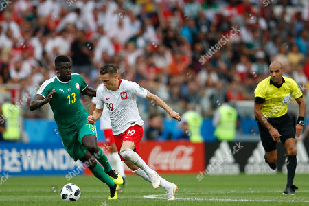 Referee Nawaf Shukralla from Bahrain, right watches Senegal's Alfred Ndiaye, left, and Poland's Piotr Zielinski compete for the ball during the group H match between Poland and Senegal at the 2018 soccer World Cup in the Spartak Stadium in Moscow, Russia