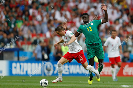 Poland's Piotr Zielinski, left, runs with the ball followed by Senegal's Alfred Ndiaye during the group H match between Poland and Senegal at the 2018 soccer World Cup in the Spartak Stadium in Moscow, Russia
