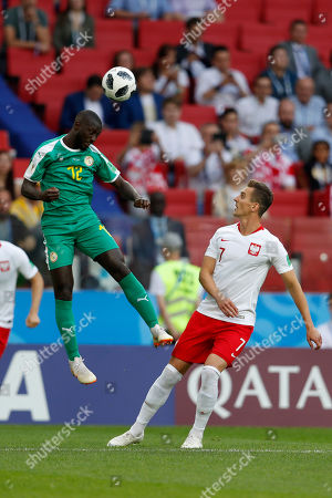 Senegal's Moussa Konate, left, heads the ball past Poland's Arkadiusz Milik during the group H match between Poland and Senegal at the 2018 soccer World Cup in the Spartak Stadium in Moscow, Russia