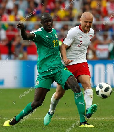 Senegal's Cheikh Ndoye, left, challenges for the ball Poland's Michal Pazdan, right, during the group H match between Poland and Senegal at the 2018 soccer World Cup in the Spartak Stadium in Moscow, Russia