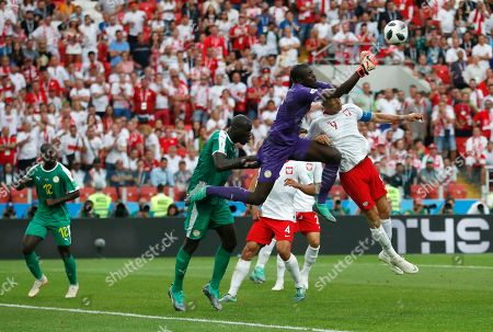 Senegal goalkeeper Khadim Ndiaye, center, makes a play on the ball ahead of Poland's Robert Lewandowski, right, during the group H match between Poland and Senegal at the 2018 soccer World Cup in the Spartak Stadium in Moscow, Russia