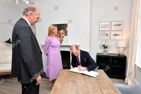 Nick Wentworth-Stanley and Clare Mountbatten look-on as Prince William signs the guest book during a visit to James' Place in Liverpool
