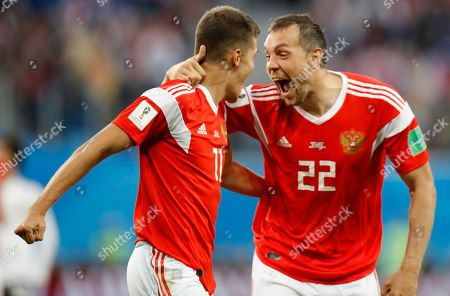Artyom Dzyuba, Roman Zobnin, Ahmed Fathy. Russia's Artyom Dzyuba, right, and Roman Zobnin celebrate after Egypt's Ahmed Fathy scoring the own goal, the opening goal of the group A match between Russia and Egypt at the 2018 soccer World Cup in the St. Petersburg stadium in St. Petersburg, Russia