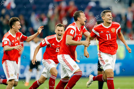 Russia's Alexander Golovin, Denis Cheryshev, Artyom Dzyuba, Roman Zobnin, Ahmed Fathy. From left: Russia's Alexander Golovin, Denis Cheryshev, Artyom Dzyuba, and Roman Zobnin celebrate after Egypt's Ahmed Fathy scoring the own goal, the opening goal of the group A match between Russia and Egypt at the 2018 soccer World Cup in the St. Petersburg stadium in St. Petersburg, Russia