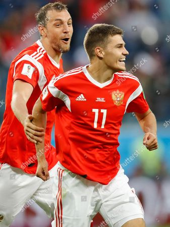 Artyom Dzyuba, Roman Zobnin, Ahmed Fathy. Russia's Artyom Dzyuba, left, and Roman Zobnin celebrate after Egypt's Ahmed Fathy scoring the own goal, the opening goal of the group A match between Russia and Egypt at the 2018 soccer World Cup in the St. Petersburg stadium in St. Petersburg, Russia