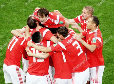 Russia players celebrate after Roman Zobnin of Russia sees his shot deflect off Ahmed Fathy of Egypt for an own goal.
