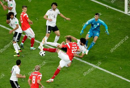Russia's Artyom Dzyuba, center, and Egypt's Ali Gabr, behind, jump fighting for the ball as Egypt goalkeeper Mohamed Elshenawy, left, gets ready to save a goal during the group A match between Russia and Egypt at the 2018 soccer World Cup in the St. Petersburg stadium in St. Petersburg, Russia