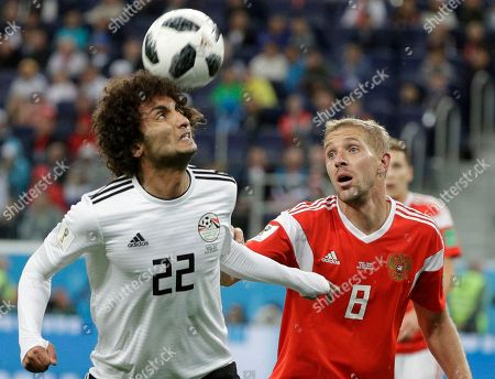 Russia's Yuri Gazinsky, right, challenges for the ball with Egypt's Amr Warda during the group A match between Russia and Egypt at the 2018 soccer World Cup in the St. Petersburg stadium in St. Petersburg, Russia