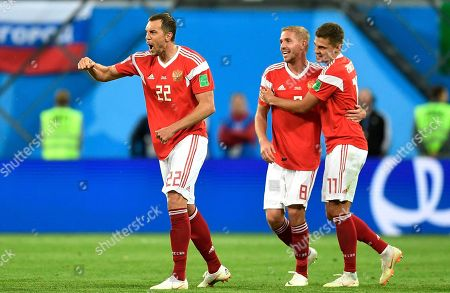 Russia's Artyom Dzyuba, left, celebrates after scoring his side's third goal with teammates Roman Zobnin and Yuri Gazinsky, from right, during the group A match between Russia and Egypt at the 2018 soccer World Cup in the St. Petersburg stadium in St. Petersburg, Russia