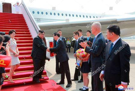 """Stock Photo of Ri Sol Ju, Kim Jong Un, Wang Huning. Provided on June 20, 2018, by the North Korean government, North Korean leader Kim Jong Un, second from left, and his wife Ri Sol Ju, left, are greeted by Wang Huning, member of the Politburo Standing Committee, on their arrival at Beijing Capital International Airport in Beijing, China. Korean language watermark on image as provided by source reads: """"KCNA"""" which is the abbreviation for Korean Central News Agency"""