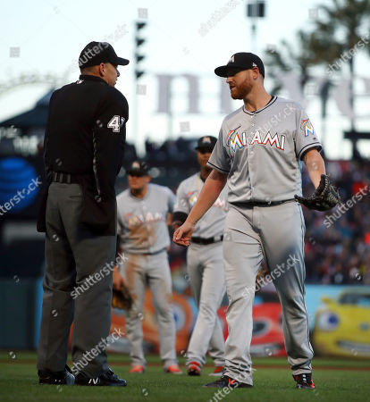 Andy Fletcher, Dan Straily. Miami Marlins pitcher Dan Straily, right, speaks with home plate umpire Andy Fletcher after Straily hit San Francisco Giants' Buster Posey with a pitch and was ejected by Fletcher during the second inning of a baseball game, in San Francisco