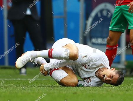 Cristiano Ronaldo of Portugal feels the pain from a challenge by Mehdi Benatia of Morocco