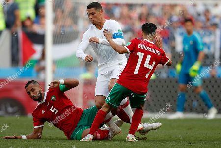 Morocco's Mehdi Benatia, left, and Morocco's Mbark Boussoufa, right, challenge Portugal's Cristiano Ronaldo, center, during the group B match between Portugal and Morocco at the 2018 soccer World Cup in the Luzhniki Stadium in Moscow, Russia