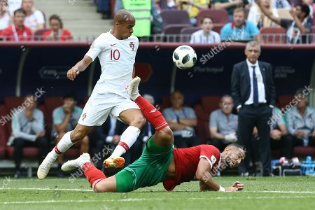 Joao Mario (L) of Portugal in action against Mehdi Benatia (R) of Morocco during the FIFA World Cup 2018 group B preliminary round soccer match between Portugal and Morocco in Moscow, Russia, 20 June 2018. (RESTRICTIONS APPLY: Editorial Use Only, not used in association with any commercial entity - Images must not be used in any form of alert service or push service of any kind including via mobile alert services, downloads to mobile devices or MMS messaging - Images must appear as still images and must not emulate match action video footage - No alteration is made to, and no text or image is superimposed over, any published image which: (a) intentionally obscures or removes a sponsor identification image; or (b) adds or overlays the commercial identification of any third party which is not officially associated with the FIFA World Cup)