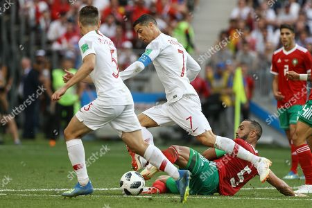 Cristiano Ronaldo (C) of Portugal in action against Mehdi Benatia (R) of Morocco during the FIFA World Cup 2018 group B preliminary round soccer match between Portugal and Morocco at the Luzhniki Stadium, in Moscow, Russia, 20 June 2018. (RESTRICTIONS APPLY: Editorial Use Only, not used in association with any commercial entity - Images must not be used in any form of alert service or push service of any kind including via mobile alert services, downloads to mobile devices or MMS messaging - Images must appear as still images and must not emulate match action video footage - No alteration is made to, and no text or image is superimposed over, any published image which: (a) intentionally obscures or removes a sponsor identification image; or (b) adds or overlays the commercial identification of any third party which is not officially associated with the FIFA World Cup)