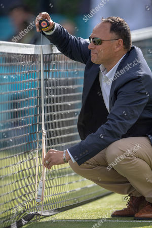 Umpire Mohamed Lahyani measures and adjusts the height of the net during the match between Marin Cilic (CRO) and Gilles Muller (LUX).  Fever-Tree Tennis Championships, Queens Tennis Club, London, England, 20th June 2018.