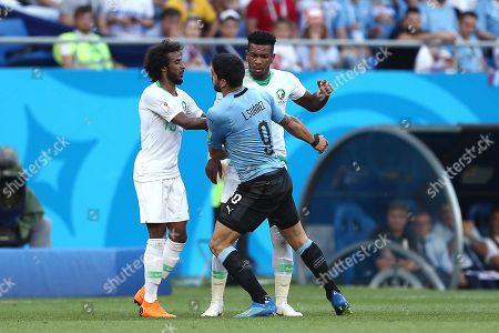 Luis Suarez of Uruguay reacts to Yasser Al-Shahrani of Saudi Arabia