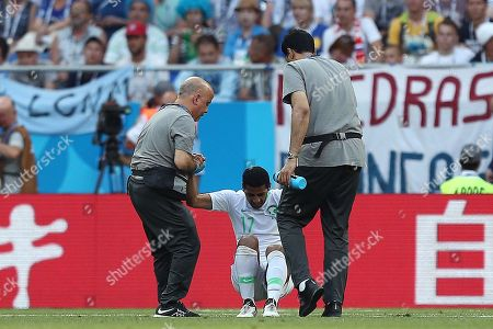 Taisir Al-Jassim of Saudi Arabia is helped from the pitch after injuring his hamstring