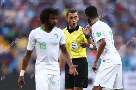 Referee Clement Turpin speaks with Salman Al-Faraj of Saudi Arabia