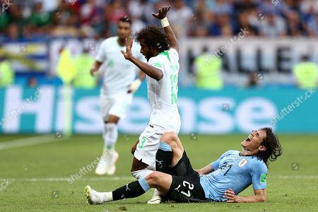 Edison Cavani of Uruguay reacts to tackle by Yasser Al-Shahrani of Saudi Arabia