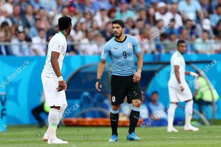 Luis Suarez of Uruguay and Ali Al-Bulaihi of Saudi Arabia exchange words