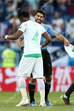 Ali Al-Bulaihi of Saudi Arabia and Luis Suarez of Uruguay at the final whistle