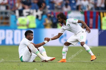 Yasser Al-Shahrani of Saudi Arabia helps Ali Al-Bulaihi to his feet after the final whistle