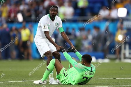 Osama Hawsawi of Saudi Arabia helps goalkeeper Mohammed Al-Owais to his feet after the final whistle