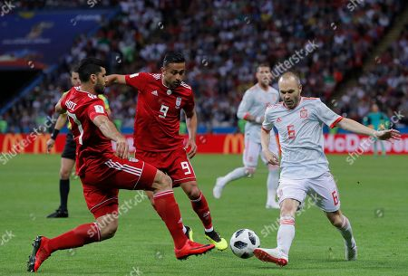 Spain's Andres Iniesta, right, fights for a ball with Iran's Omid Ebrahimi, center, and Masoud Shojaei, during the group B match between Iran and Spain at the 2018 soccer World Cup in the Kazan Arena in Kazan, Russia
