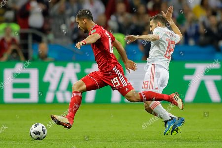 Iran's Majid Hosseini, left vies for the ball with Spain's Jordi Alba during the group B match between Iran and Spain at the 2018 soccer World Cup in the Kazan Arena in Kazan, Russia